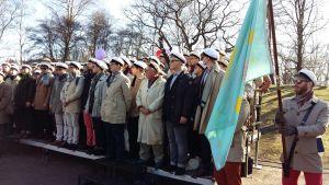 Akademiska sångföreningen uppställda i Kajsaniemiparken med studentmössor på sig.