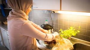 huivipäinen laittaa keittiössä ruokaa