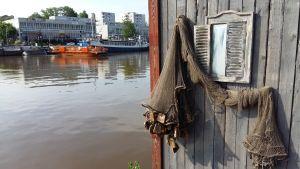 Ett fisknät pryder en trävägg just invid stadsfärjan Föri i Åbo.