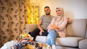 Mies ja huivipäinen nainen istuvat sohvalla