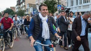 President Emmanuel Macron och hans hustru Brigitte Trogneux (till vänster bakom Macron) på cykeltur på lördagen.