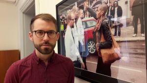Daniel Poohl bredvid en stor tavla av ett fotografi där Tess Asplund står i protest med knutnäven i luften riktad mot NMR:s marsch.