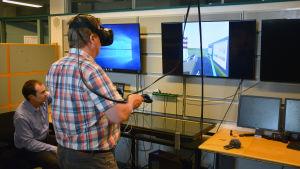 Rayko Toshev visar ett virtuellt kraftverk till John Dahlbacka.