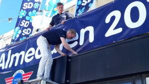 Två unga killar står uppe på en husfasad och fäster banderoller med SD-logga.