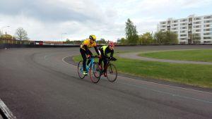 Två cyklister tränar på velodromen i Kuppisparken i Åbo.