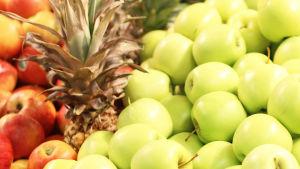 Röda äpplen, ananas och gröna äpplen i närbild.
