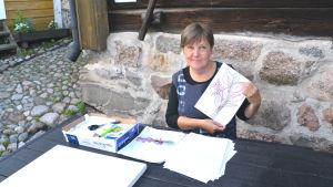 Kvinna sitter vid bord utomhus, håller upp teckning med ett trädo