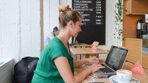 Dansare och koreograf Maria Nurmela sitter vid en laptop på IPI Kulmakuppila