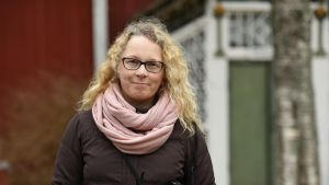 Sara Bondegård framför en gård men röda väggar och en grön dörr.