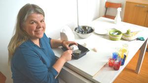 Kvinna i blått sitter vid bord och skrapar med kniv mot sten. Hon ler mot kameran.
