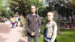 ung man i svarta kläder och ung kvinna i ljusa kläder står framför Porthans staty i Åbo. I bakgrunden människor med regnbågsflaggor