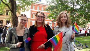 Tre unga kvinnor med regnbågsflaggor i händerna står framför Katedralskolan i Åbo
