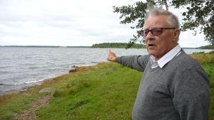 Håkan Södergård står vid stranden och pekar ut mot Storgrynnan i Pjelax som har förstörts av skarvar.