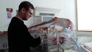 En pappa sköter sin för tidigt födda baby i en kuvös.