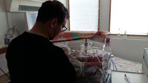 En pappa sköter sin för tidigt födda baby som ligger i en kuvös.