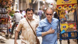YOgi och Göran på går på en trång gata i Indien.