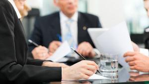 Människor sitter kring ett arbetsbord under ett möte.