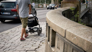 En pappa med barnvagn går längs en trottoar.