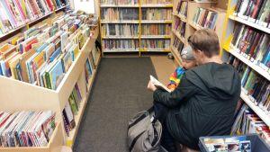En mamma läser för sitt barn ur en bok i en bokbuss.