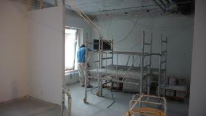 En man står intill en byggställning och målar väggar inne i ett hus.