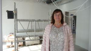 Doris Bäck i ett av de blivande klientrummen i Villa Holger. Bakom henne hänger ledningar från taket och en byggställning är uppställd.