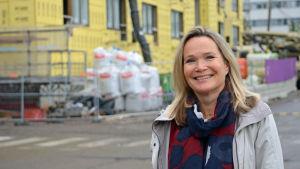Mirjam Kalland poserar framför ett halvfärdigt hus.
