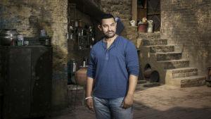 Aamir Khan framför en tegelvägg.