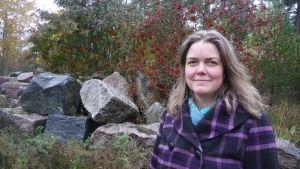 En kvinna med lila jacka står framför stora stenar och en rönn med röda bär.