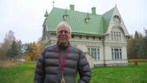 En man med glasögon står framför en gammal sommarvilla med ljus fasad och grönt plåttak.