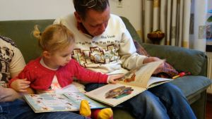 Farfar/morfar läser bok tillsammans med barnbarn
