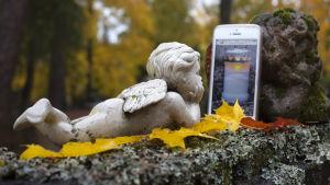 En liggande ängel på en gravsten tittar på en mobil med bilden av ett gravljus.