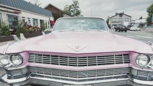 Dollargrinet på en rosa Cadillac.