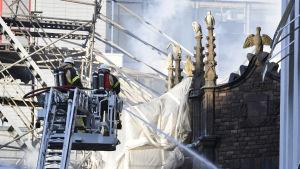 Två brandmän på en lyftkran sprutar vatten över ett rykande hus.