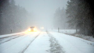 Bil på Strandvägen syns knappt i snöstormen.
