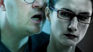 En man står bakom en kvinna och viskar något i örat. Kvinnan ser oroad ut.