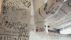 Vita väggar och ventilationsrör täckta med graffiti och texter skrivna med tuschpenna.