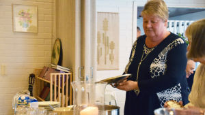En kvinna står med ett kastrulllock i handen vid en bord där det serveras mat. Brevid henne står en annan kvinna och tar åt sig mat. Kvinnan på bilden heter Mona Andersson.