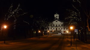 Julbelysning pryder ljusen längs med en gata i Kristinestad. I bakgrunden syns ett vitt stort hus.