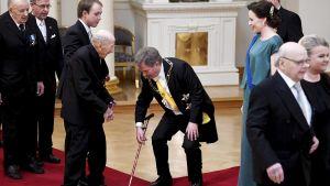 President Sauli Niinistö lyfter krigsveteranen Arvo Pusas vandringskäpp under slottsbalen.