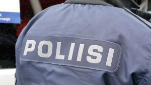 """Polis, fotograferad bakifrån så att texten """"poliisi"""" syns på ryggen."""