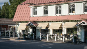 Vanha valkoinen puutalo jolla punainen peltikatto, talossa ravintola ja talon edustalla terassi.