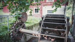 Puinen myllynratas ja hammaspyörät, taustalla punamullattu talo jossa kivijalka.