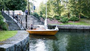 Segelbåt i trä kommer ut ur kanal.