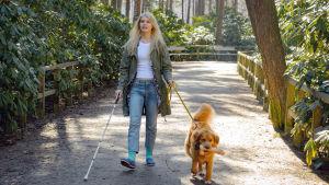 Näkövammaista Donnaa näyttelevä Alina Tomnikov kävelee puistossa koira toisessa kädessä hihnassa, valkoinen keppi toisessa. Koira kantaa suussaan dildoa kuin keppiä.