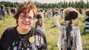 Hiljainen kansa -teoksen yhteydessä toimivan Niittykahvilan pitäjä Ritva Huttunen heinäseiväshahmojen keskellä.