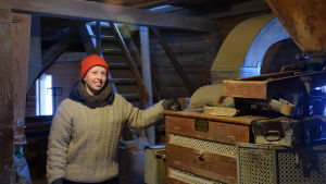 Anna Alm står vid en maskin som skalar spannmål.