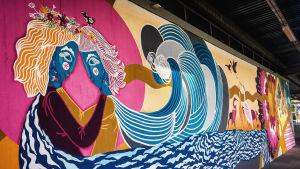 seinämaalaus Martinlaakson juna-aseman odotuslaiturilla, kaksi syleilevää hahmoa, aaltoja.