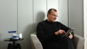 En man med glasögon sitter i en fåtölj och pillar på en iPad.