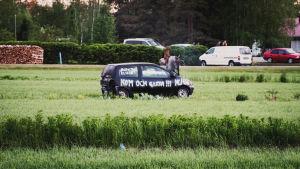 """En svart bil ute på en åker som har texter sprayade på den som t.ex. """"Kom och gissa!"""""""