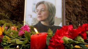 En bild på Anna Politkovskaya. I förgrunden syns blommor vid ett minnesmärke.